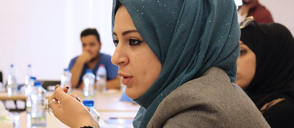 A young woman in Jordan speaks at a meeting