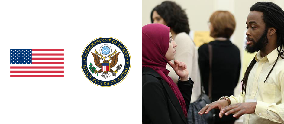 U.S. flag, seal of the U.S. Department of State, and two participants talking to each other in a meeting space
