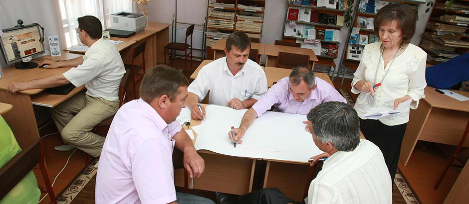 Photo of an instructor who is standing next to four seated people in a library. One person is writing on a notepad's page while the others watch.