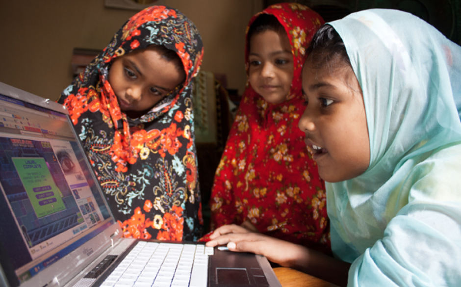 Three girls wearing headscarves and using a laptop